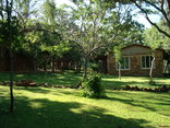 Shakati Game Reserve - The garden with one of the chalets
